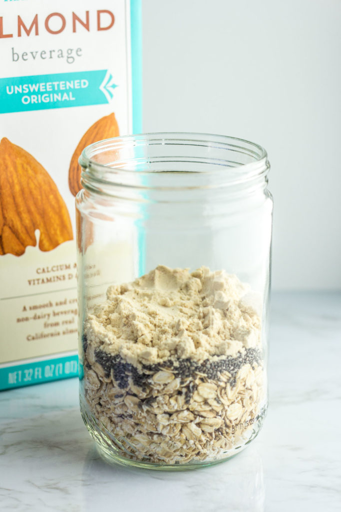 Old fashion rolled oats, chia seeds, protein powder in a clear mason jar with almond milk in the background