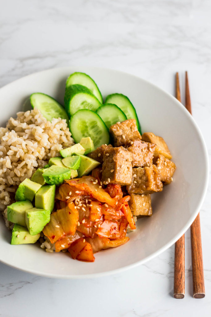 teriyaki tofu buddha bowl with stir fried kimchi, avocado, and cucumber over brown rice