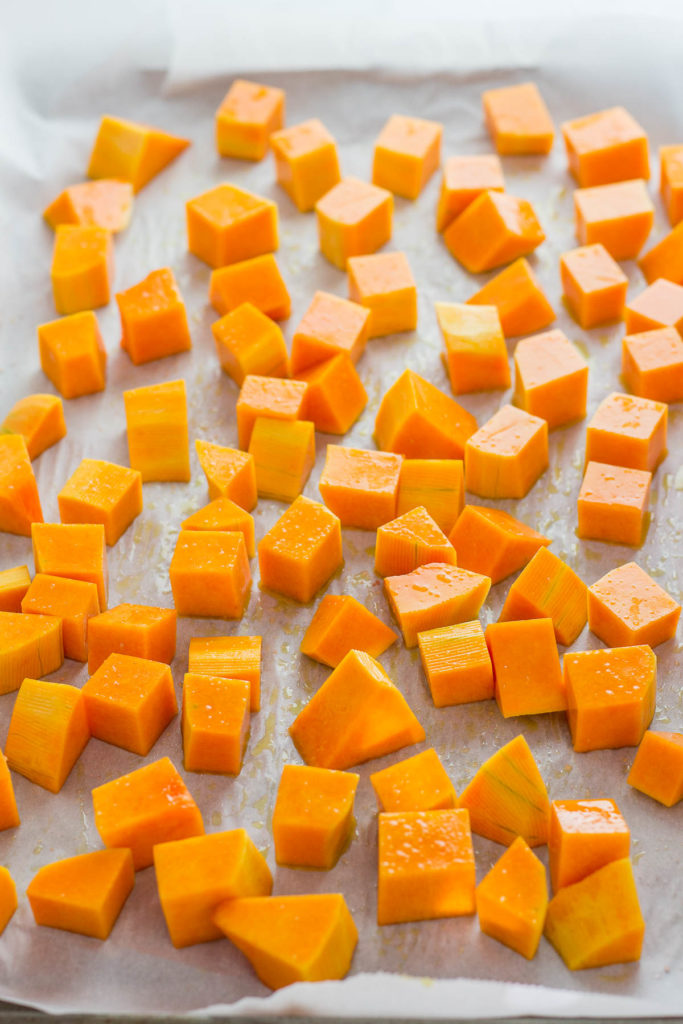 Cubed butternut squash on a baking pan before baking