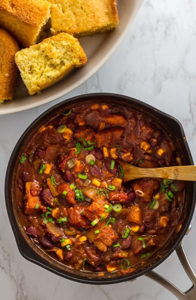 Overhead shot of pot of chili with corn bread on the side