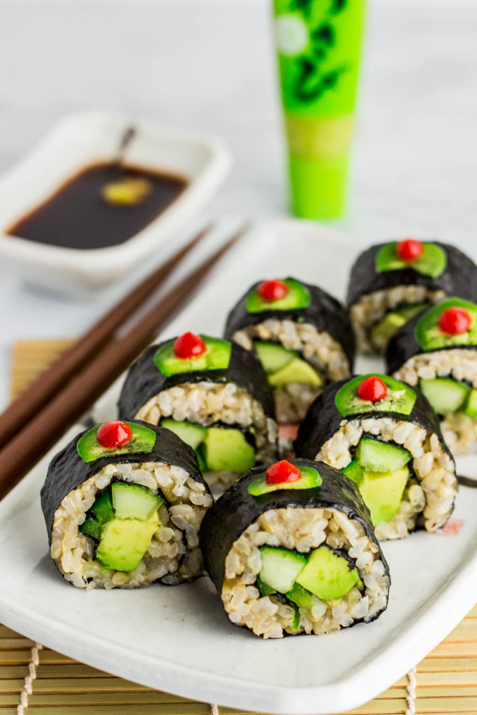 Close up shot of regular vegan green sushi roll. It is decorated with thin slice of jalapeno dotted with sriracha sauce on top of each roll.