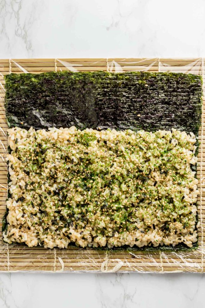 Rice is evenly spread on top of seaweed paper with seaweed flakes sprinkled on top. About one third of the seaweed paper is left empty and not covered with rice.
