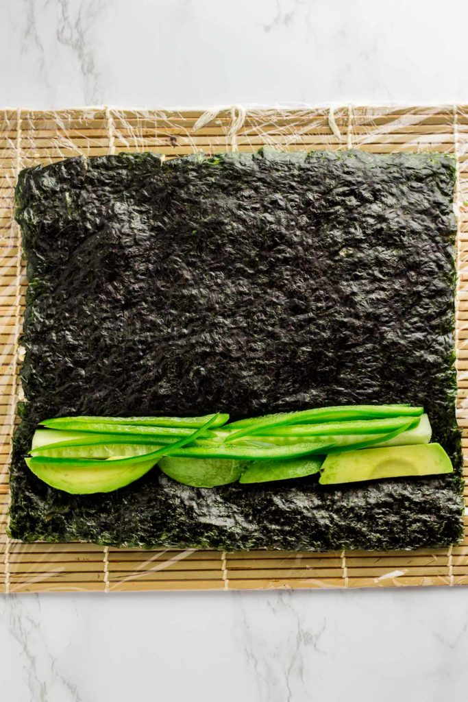 Cucumber, avocado, and jalapeno are added on top of seaweed paper that has been flipped over once the rice was spread on top