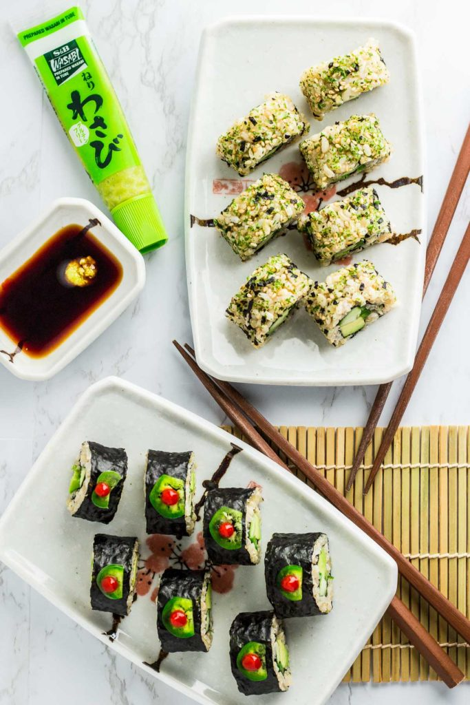 Over head shot of both inside out and regular vegan green sushi rolls. Two pair of chopsticks and soy sauce with wasabi paste is next to the rolls.