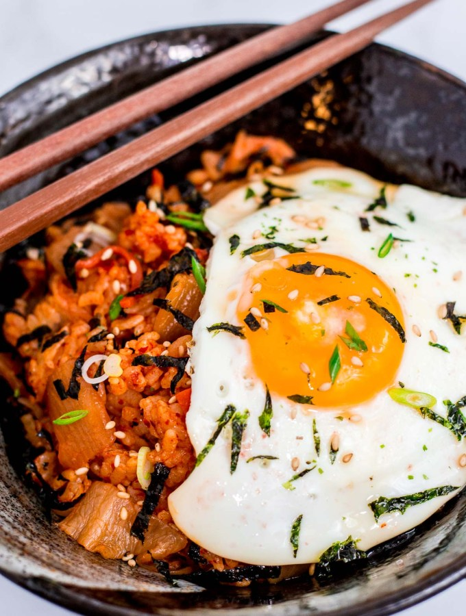 another picture of bowl full of kimchi fried rice with fried egg and seaweed paper strips and green onion as garnish
