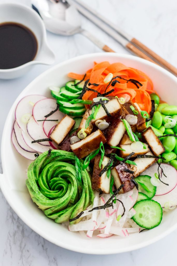 Shot of hoisin tofu sushi bowl, pair of chopsticks, spoon, and soy sauce in the background