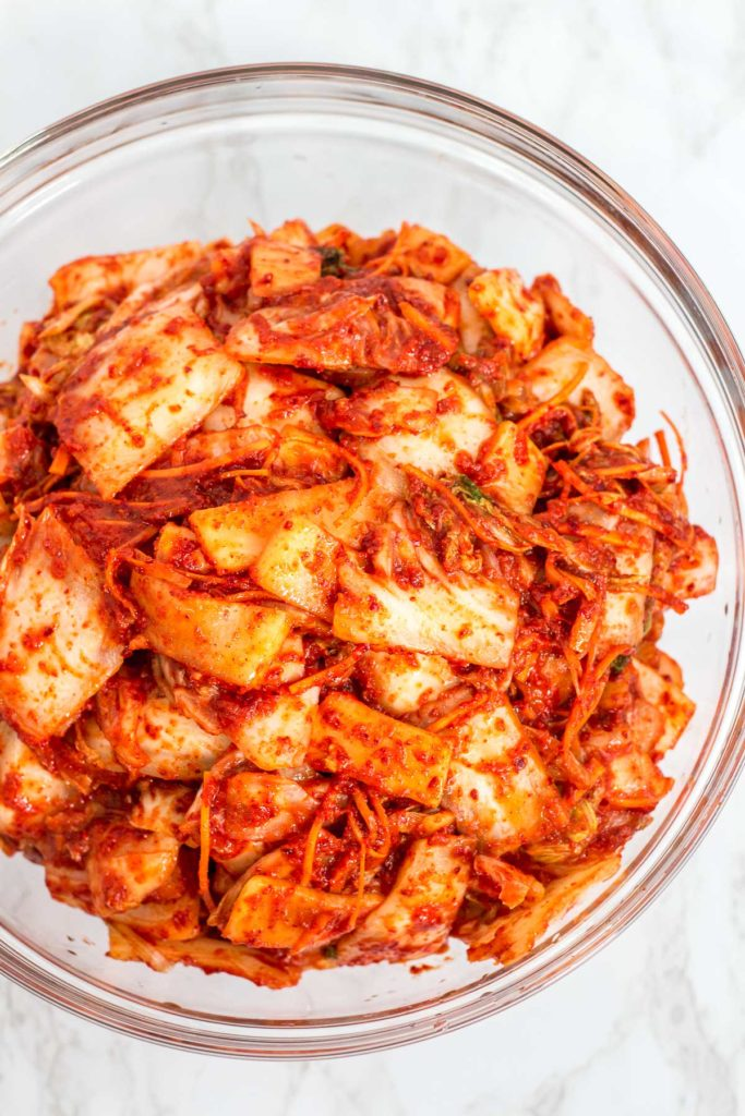 A large bowl of mixed homemade vegan kimchi, ready to be transferred to a container with a lid
