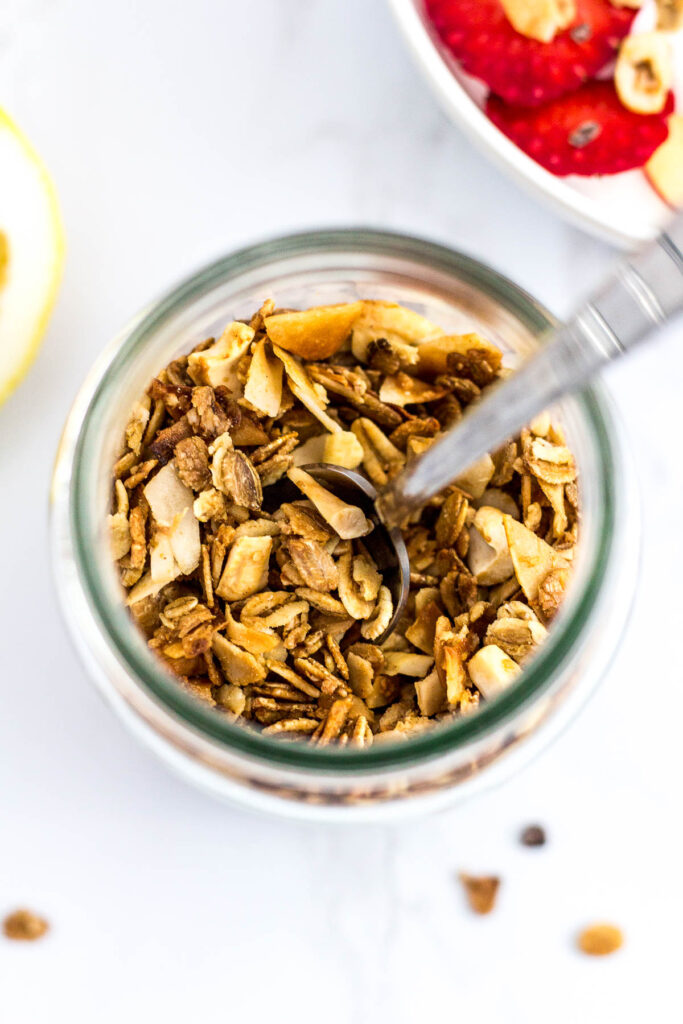 Overhead shot of small batch cashew coconut granola in a clear glass jar with the spoon sticking out