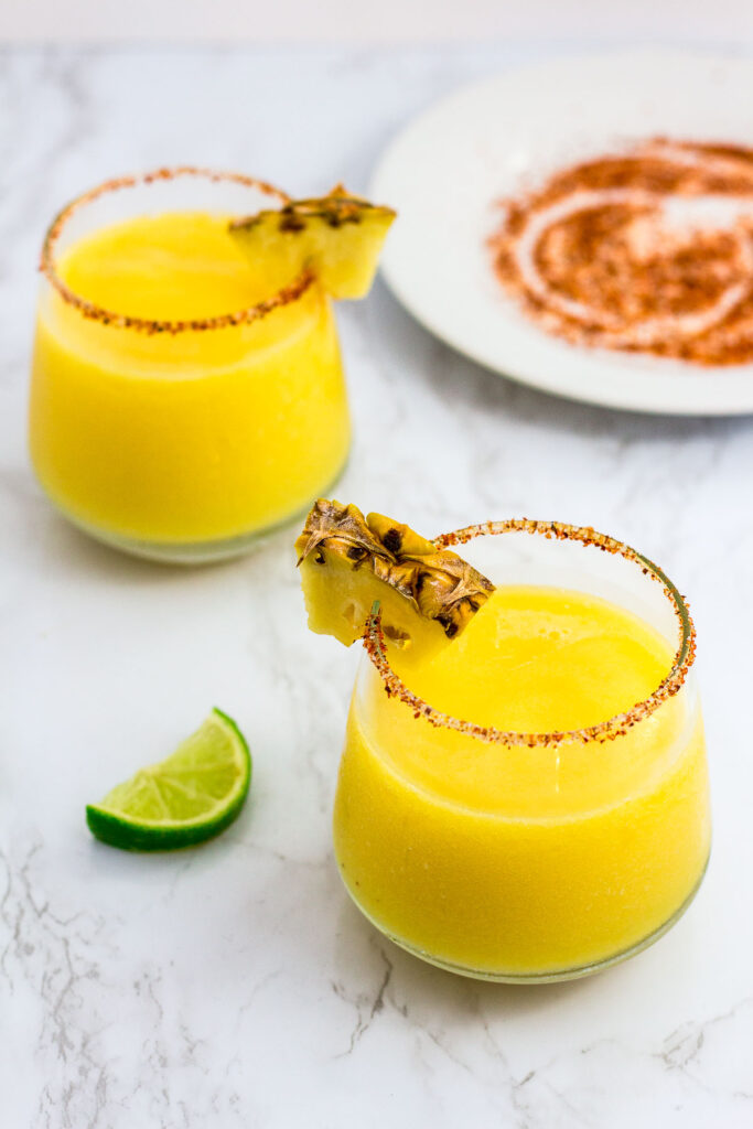 two glasses of margarita with Tajin salt on the plate