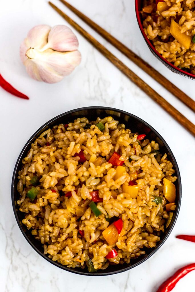 over head shot of fried rice in the black bowl with chopsticks next to it