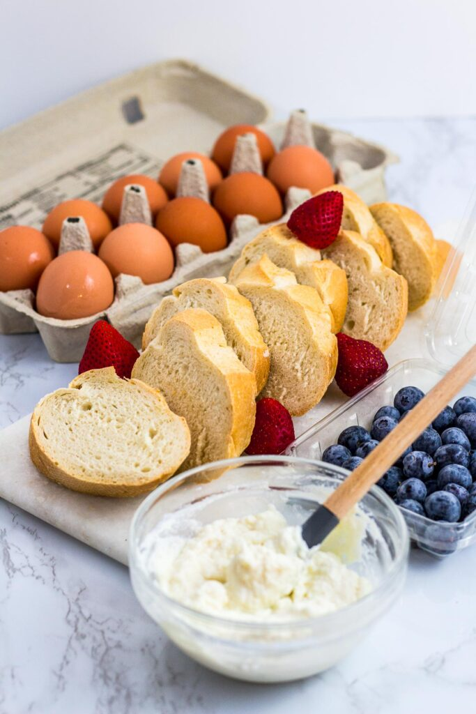 a carton of eggs, sliced baguette bread, sweet ricotta cheese and blueberries