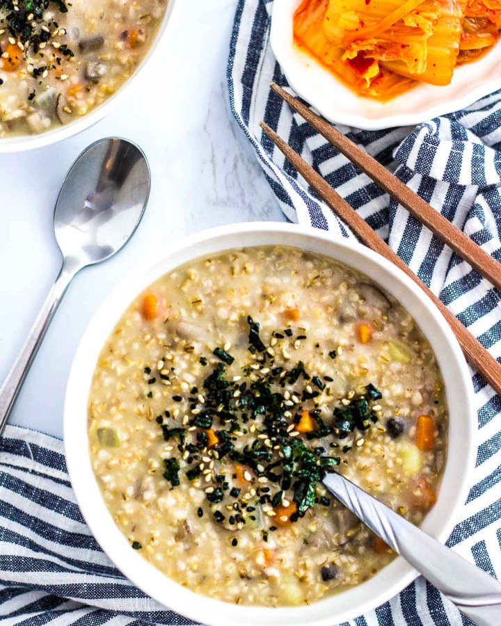 two bowls of vegan savory steel cut oatmeal with side of kimchi