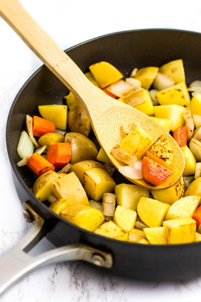 browned potato and carrot pieces with onion in the skillet