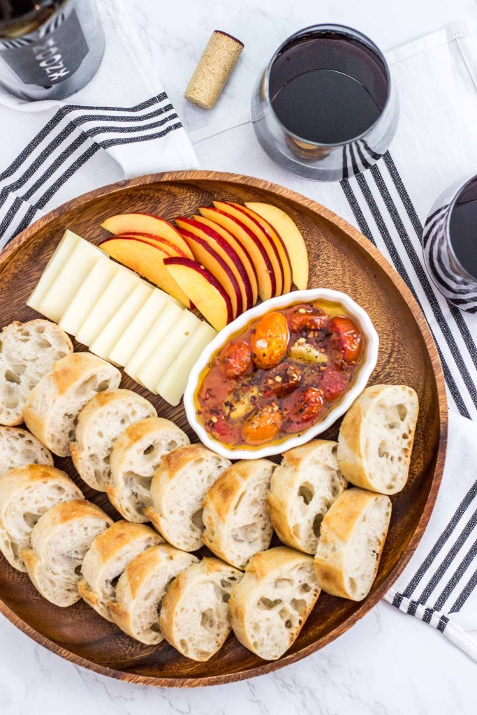platter of cherry tomato and garlic bread oil with baguette, cheese, and fruit
