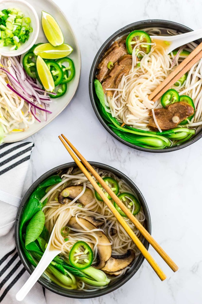 overhead shot of two bowls of vegan pho, one with seitan slices and the other with mushroom