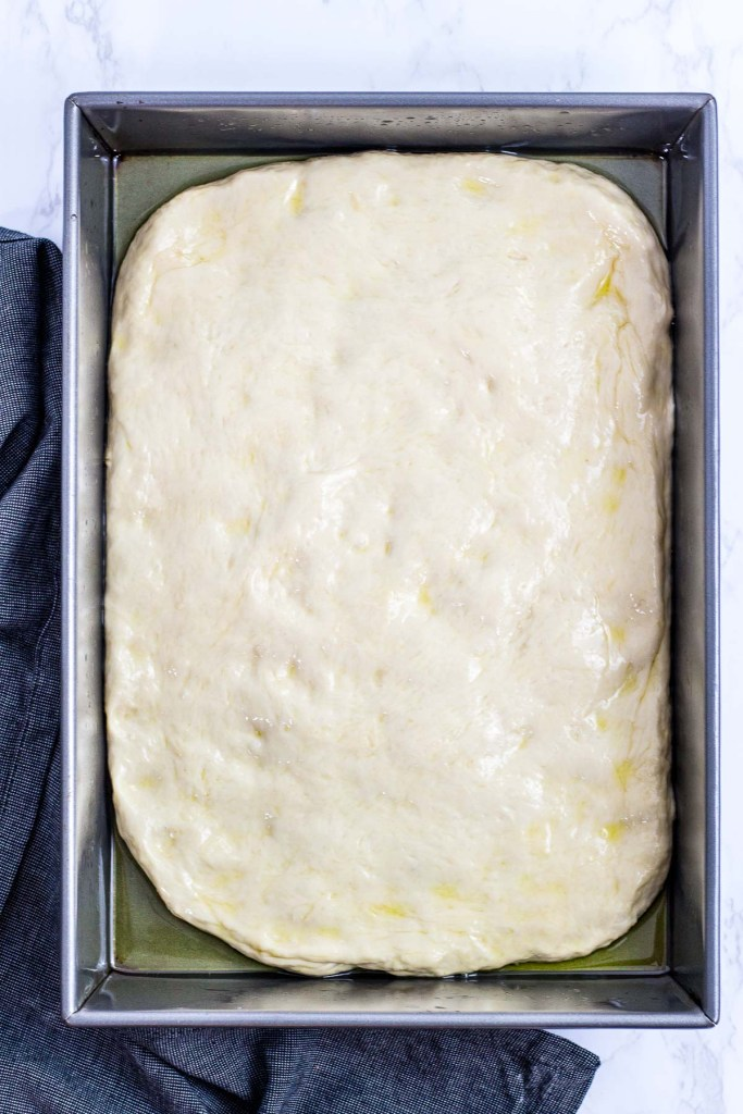 Pizza dough before rising in the baking pan