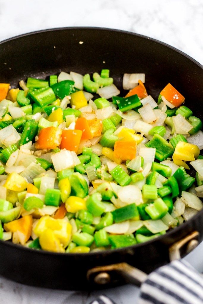 Onion, celery, garlic, and bell pepper being sautéed in the pan