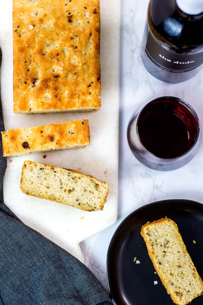 overhead shot of small batch garlic green onion focaccia with red wine