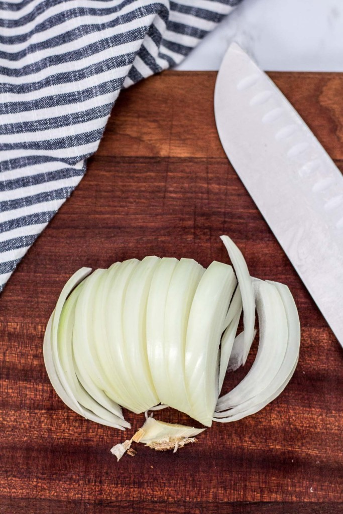 overhead shot of sliced onion, the beard part of the onion removed