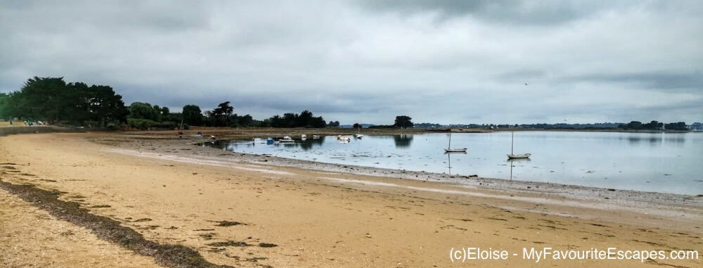An empty beach at low tide on the Ile d'Arz, with sailing boats in the bay