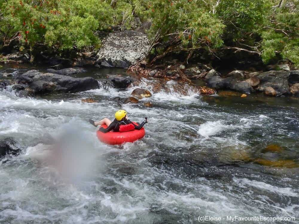Woman in a red buoy going down the rapids in a river close to Cairns