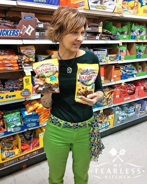 a woman in green pants and a black top holding bags of raisinets