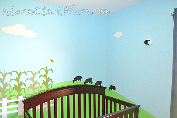 grazing cows behind the crib in a farm-themed nursery
