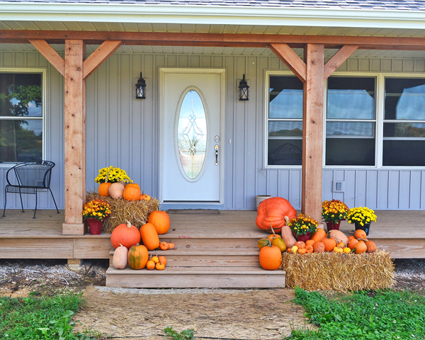 front porch decorated for fall with pumpkins, mums, and straw bales