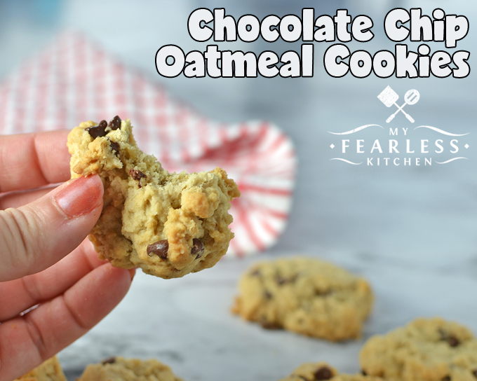 a hand holding a chocolate chip oatmeal cookie with a bite taken