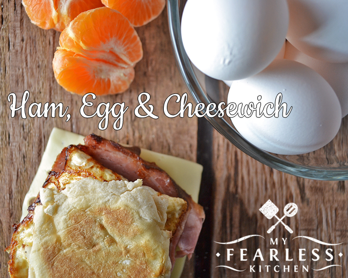 ham, egg, and cheese sandwich on an english muffin with a peeled orange and a bowl of eggs