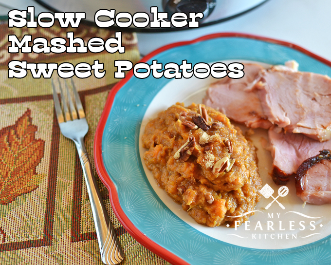 mashed sweet potatoes topped with pecans on a plate with thick ham slices