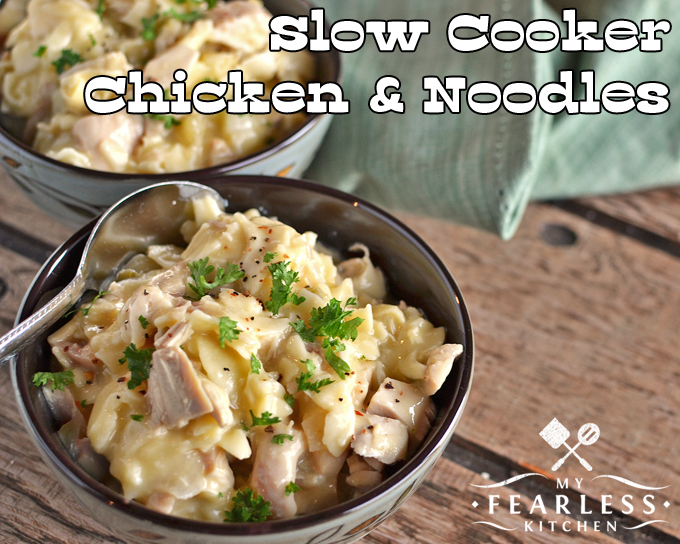 2 bowls of slow cooker chicken and noodles topped with fresh parsley