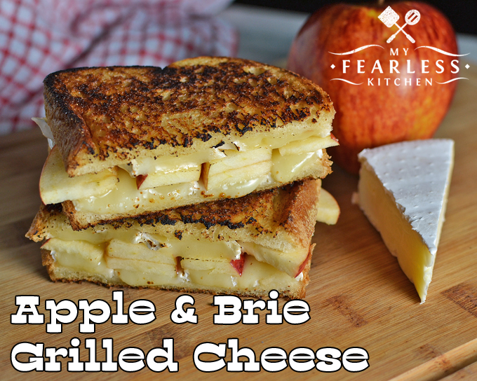 stack of apple and brie grilled cheese sandwiches with a wedge of brie and an apple