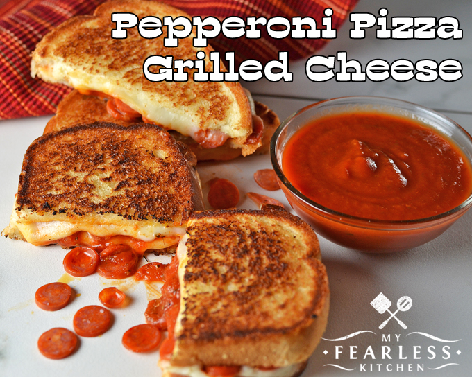 two pepperoni pizza grilled cheese sandwiches with extra pepperoni and dipping sauce