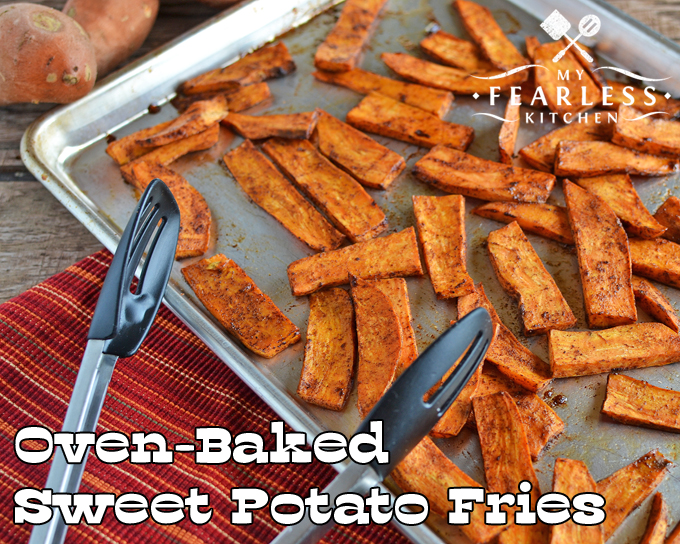oven baked sweet potato fries on a baking sheet with a red and orange tablecloth