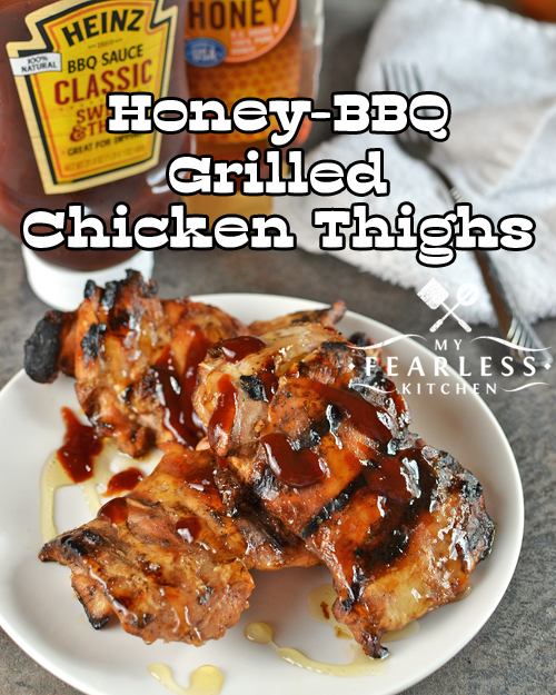 honey-bbq grilled chicken thighs on a white plate drizzled with extra honey and barbecue sauce