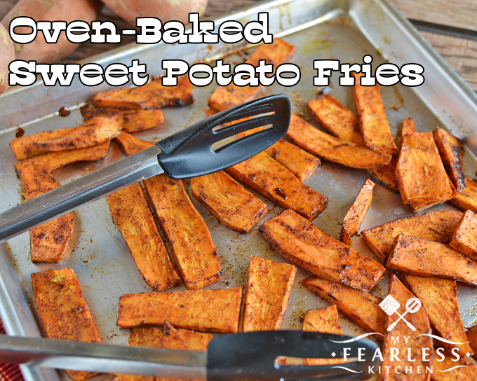 a tray of oven-baked sweet potato fries with silicone-tipped tongs