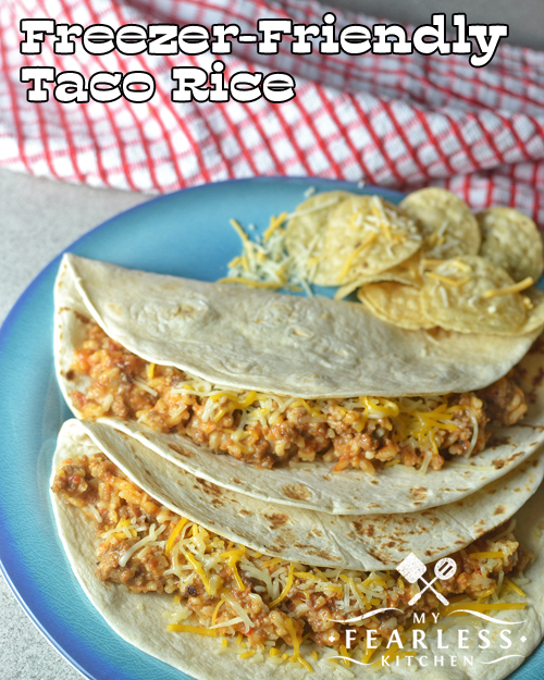 soft tacos filled with ground beef and rice on a blue plate with a red plaid napkin