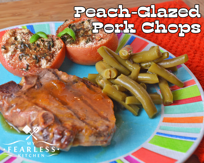 thick-cut peach-glazed pork chop on a bright plate with green beans and balsamic grilled tomatoes