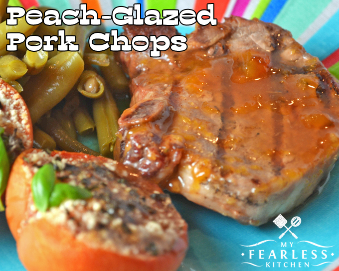 a peach-glazed pork chop with a grilled tomato and green beans on a bright plate