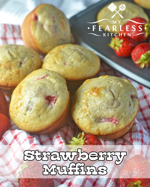 a pile of strawberry muffins with fresh strawberries with more muffins in a muffin tin in the background