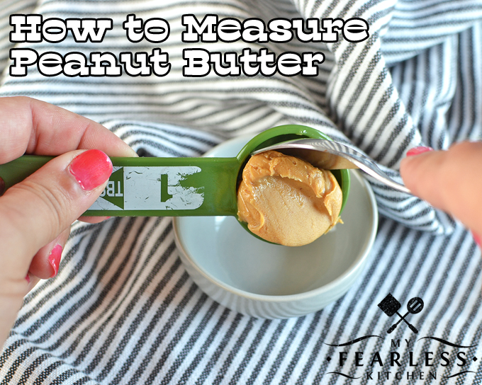 a hand holding a measuring spoon with peanut butter