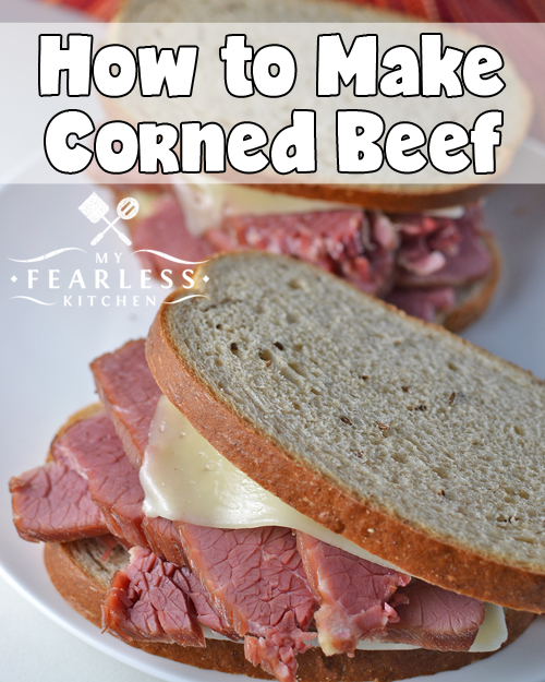 two sandwiches piled high with thick-sliced corned beef and melted swiss cheese on rye bread