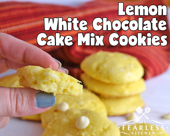 A hand holding a Lemon White Chocolate Cake Mix Cookie with a bite taken out against a red and orange background