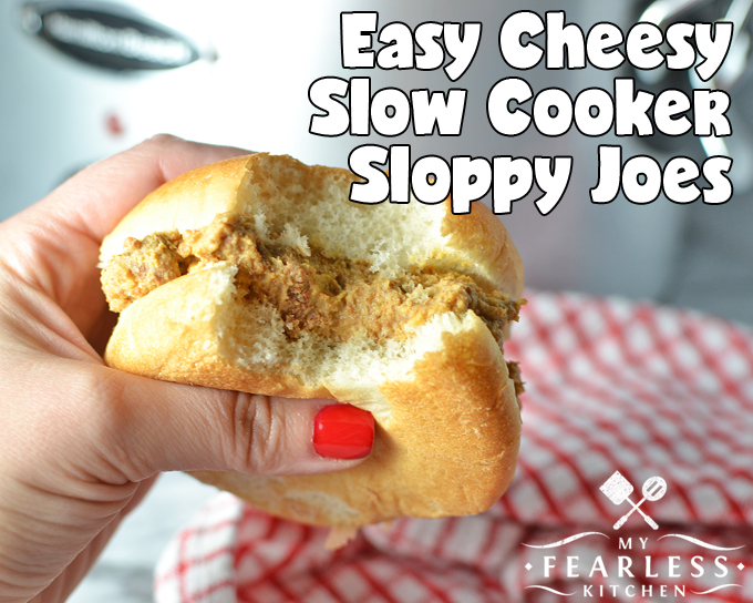 hand holding a cheesy slow cooker sloppy joe with a bite taken out
