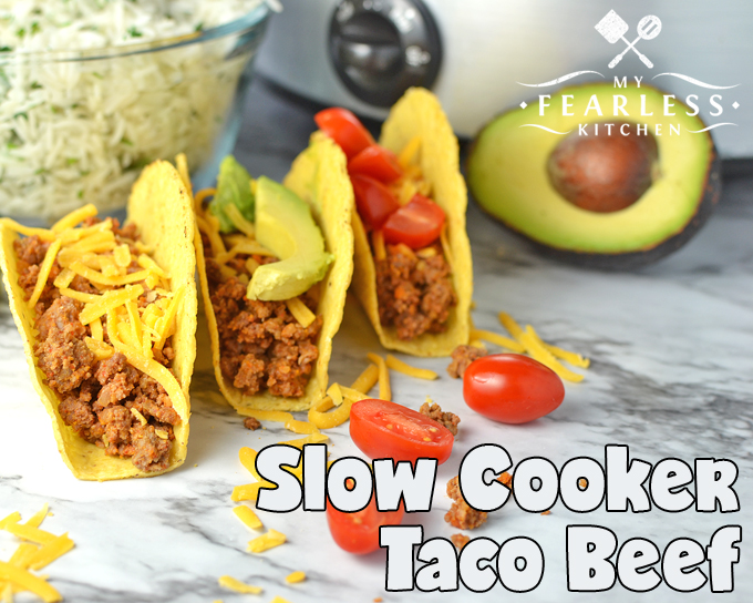 three beef tacos in hard shells topped with cheese, avocado slices, and tomato