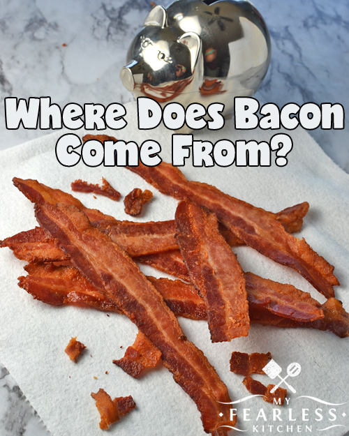 crisply cooked bacon strips on a paper towel on a marble background with a shiny silver pig