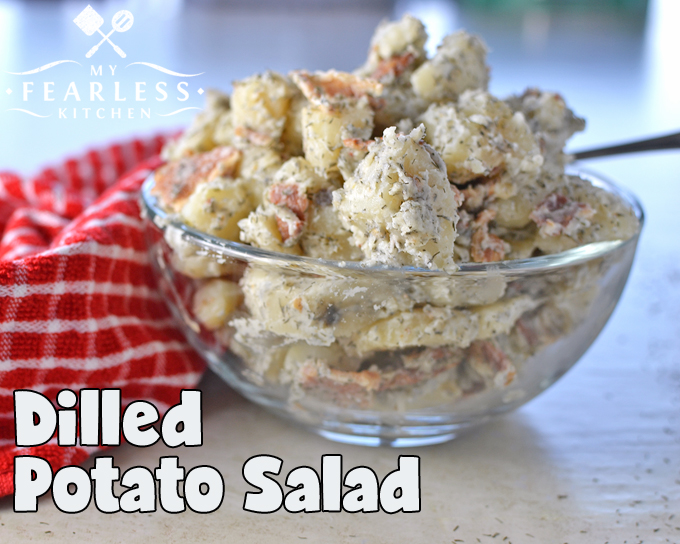 side view of potato salad with dill and bacon in a glass bowl