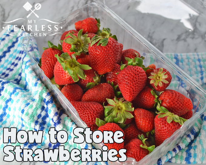 red strawberries in a plastic clamshell box on a blue and white towel on a marble background