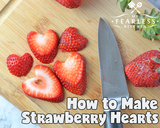 a strawberry sliced into heart shapes on a wooden cutting board